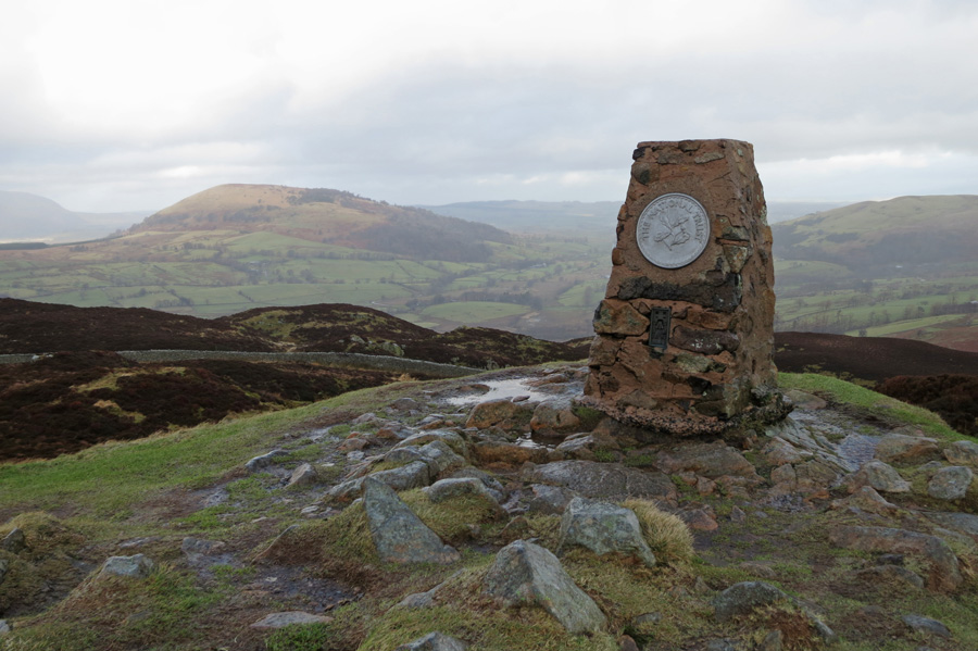 A wet and windy Gowbarrow Fell summit with Great Mell Fell in the distance