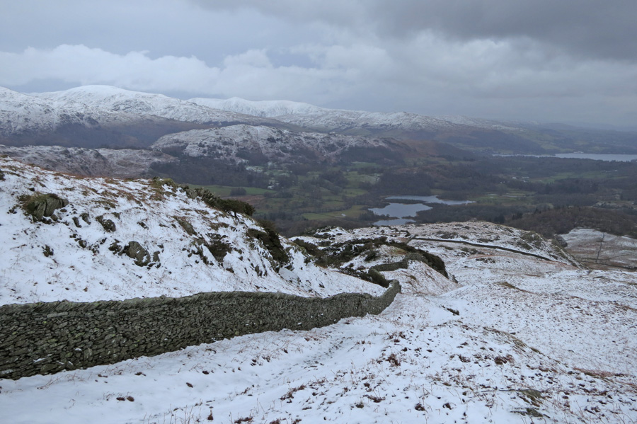 The great wall of Lingmoor Fell with Elter Water and Windermere in the distance