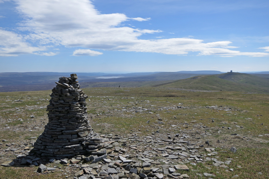 On of the large cairns with Cow Green Reservoir and Great Dun Fell  with the radar station in the distance