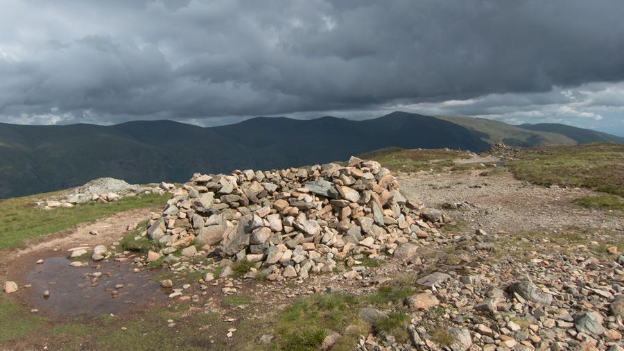 Bleaberry Fell summit shelter with Helvellyn ridge in the distance